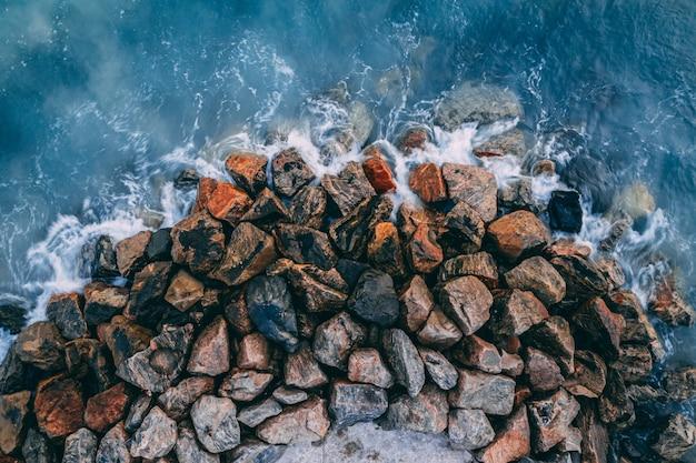 Draufsicht der meereswellen, die auf küstensteinen brechen Kostenlose Fotos