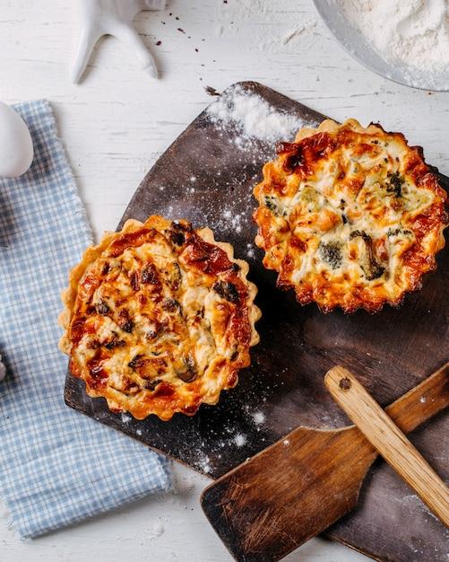 Draufsicht der minikuchen mit fleisch und gemüse auf einem hölzernen schneidebrett Kostenlose Fotos