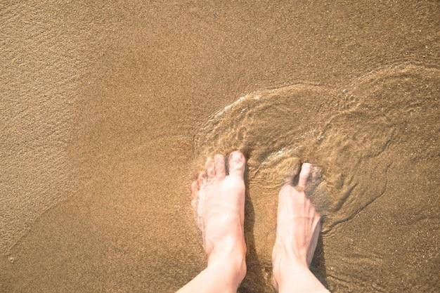 Draufsicht der nahaufnahme von füßen im nassen sand Kostenlose Fotos