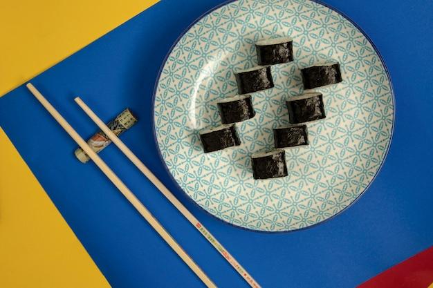 Draufsicht der nori sushirollenplatte, der essstäbchen auf blauem und gelbem hintergrund Kostenlose Fotos