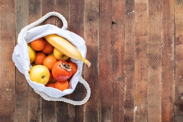 Draufsicht der ökologischen weißen leinentasche reifen fruitson alten holztischs. Premium Fotos