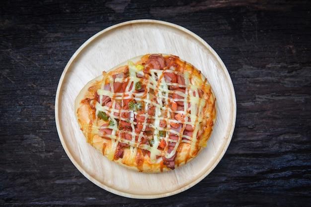 Draufsicht der pizzakäsesoße über rustikalen holzoberflächenpizzabelagwursthotdogketschup Premium Fotos