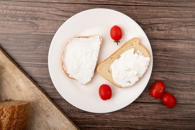 Draufsicht der platte mit brotscheiben verschmiert mit hüttenkäse und tomaten auf hölzernem hintergrund Kostenlose Fotos