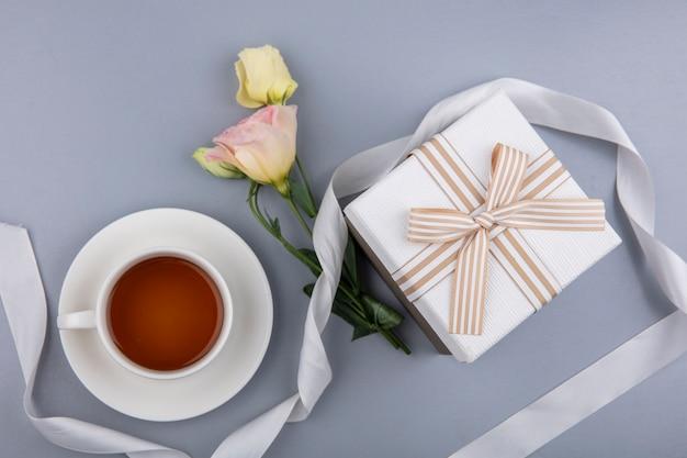 Draufsicht der reizenden blumen mit weißem geschenkboxband und einer tasse tee auf grauem hintergrund Kostenlose Fotos