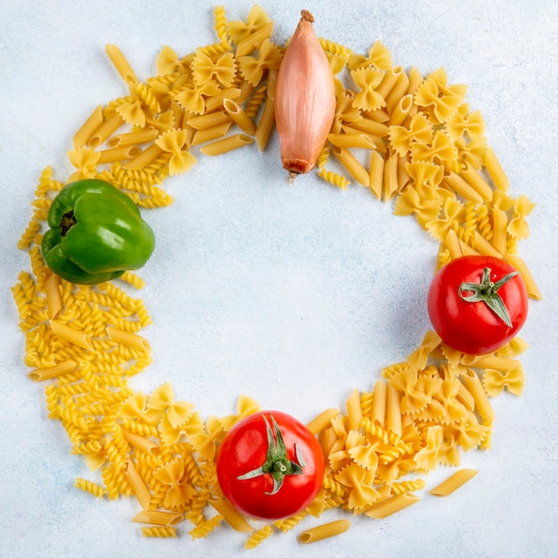 Draufsicht der rohen nudeln mit tomatenzwiebeln und paprika auf einer grauen oberfläche Kostenlose Fotos