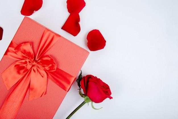 Draufsicht der roten geschenkbox gebunden mit bogen und roter farbe rose und blütenblätter auf weißem hintergrund Kostenlose Fotos
