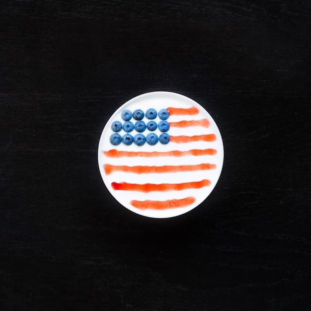 Draufsicht der schüssel mit dem joghurt, stau und blaubeeren, ausgebreitet in der amerikanischen flagge Premium Fotos