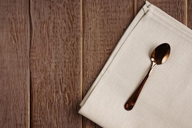 Draufsicht der stoffserviette der beige farbe und des gedienten teelöffels auf holztisch. Premium Fotos