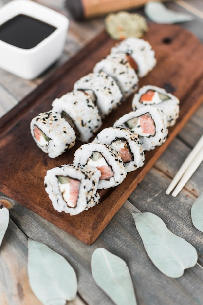 Draufsicht der sushirolle auf hölzernem behälter mit sojasoße und essstäbchen Kostenlose Fotos