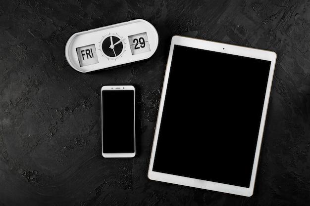 Draufsicht der tablette und des telefons auf normalem hintergrund Kostenlose Fotos