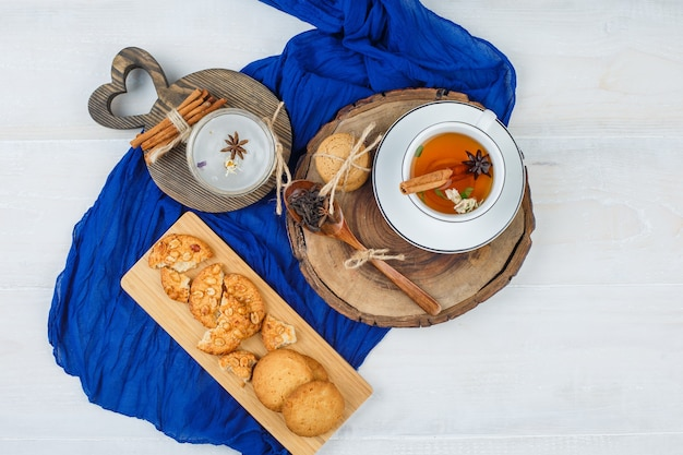 Draufsicht der tasse tee auf holzbrett mit keksen und zimt auf schneidebrettern, blauer schal auf weißer oberfläche Kostenlose Fotos