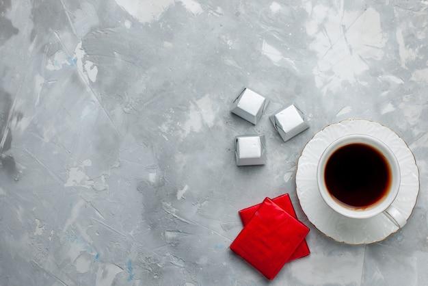 Draufsicht der tasse tee heiß in weißer tasse auf glasplatte mit silberverpackung pralinen auf hellem schreibtisch, teegetränk süße schokoladenplätzchen teatime Kostenlose Fotos
