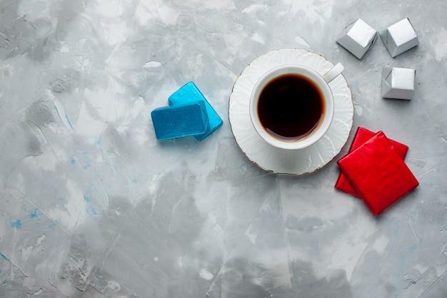 Draufsicht der tasse tee heiß in weißer tasse mit silbernen anded paket pralinen auf hellem schreibtisch, tee trinken süße keksteatime Kostenlose Fotos