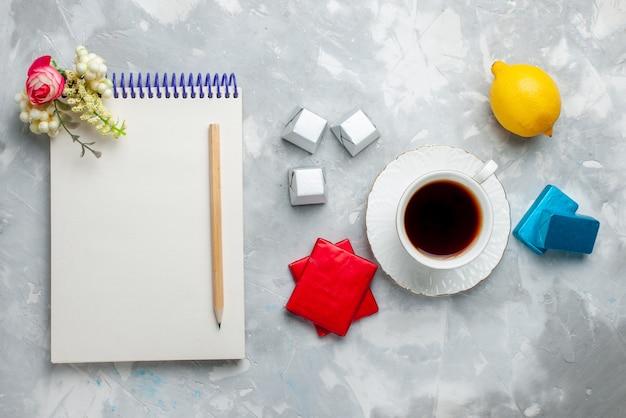Draufsicht der tasse tee heiß innerhalb der weißen tasse mit silber anded paket pralinen-notizblock auf hellem schreibtisch, trinken sie süße teezeit Kostenlose Fotos