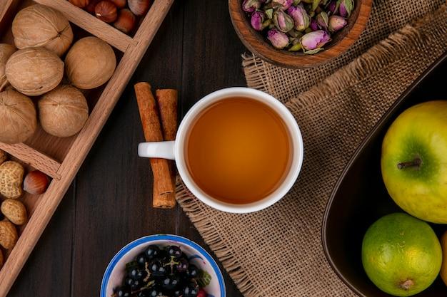Draufsicht der tasse tee mit zimtäpfeln und nüssen auf einer holzoberfläche Kostenlose Fotos
