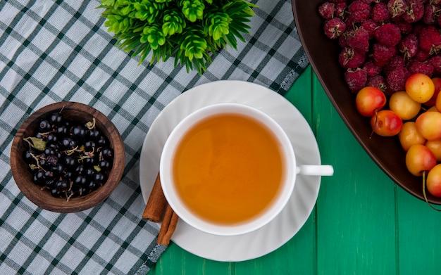 Draufsicht der tasse tee mit zimtschwarzen johannisbeeren, himbeeren und weißen kirschen auf einem karierten grünen handtuch Kostenlose Fotos