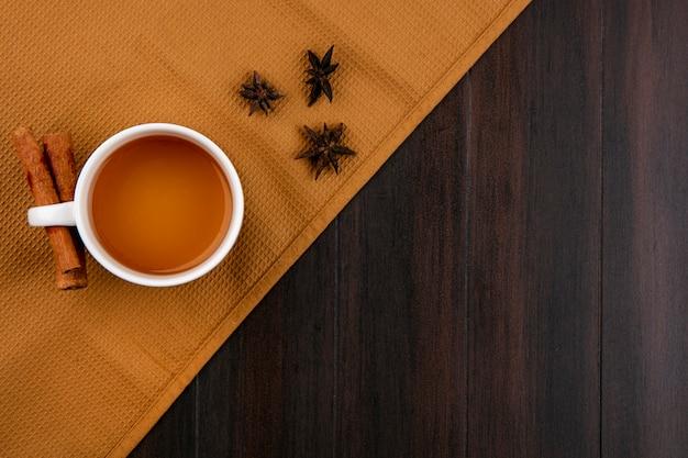 Draufsicht der tasse tee und des zimts auf einem braunen handtuch auf einer holzoberfläche Kostenlose Fotos