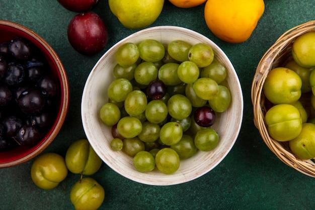 Draufsicht der traubenbeeren in schalen mit korb der pflaumen und der nectacot-pflaumen auf grünem hintergrund Kostenlose Fotos