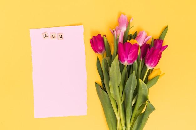 Draufsicht der tulpe blüht mit leerem papier und muttertext auf holzklötzen über gelbem hintergrund Kostenlose Fotos