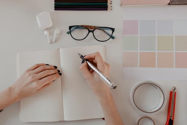 Draufsicht der weiblichen hände, die etwas im tagebuch auf von büromaterial auf weißem tisch schreiben. Kostenlose Fotos