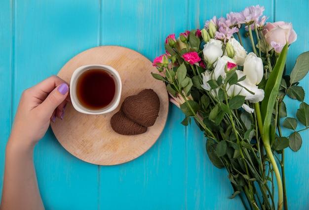 Draufsicht der weiblichen hand, die eine tasse tee auf einem hölzernen küchenbrett mit wunderbaren frischen blumen lokalisiert auf einem blauen hölzernen hintergrund hält Kostenlose Fotos