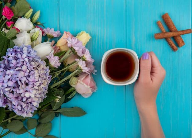 Draufsicht der weiblichen hand, die eine tasse tee mit frischen blumen der zimtstange lokalisiert auf einem blauen hölzernen hintergrund hält Kostenlose Fotos