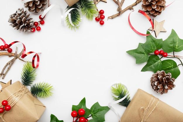 Draufsicht der weihnachtskomposition mit geschenkbox, band, tannenzweigen, zapfen, anis auf weißem tisch Kostenlose Fotos