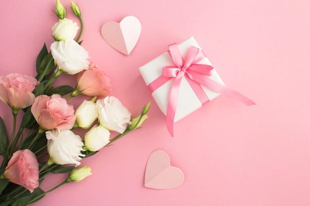 Draufsicht der weißen und rosa blumen der geschenkbox auf dem rosa hintergrund Premium Fotos