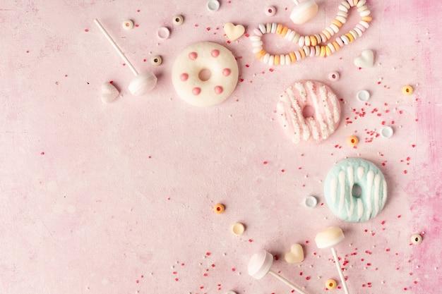 Draufsicht der zusammenstellung der glasierten schaumgummiringe und der süßigkeit mit kopienraum Premium Fotos