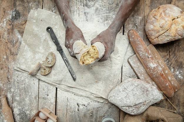Draufsicht des afroamerikanischen mannes kocht frisches müsli, brot, kleie auf holztisch Kostenlose Fotos