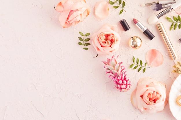 Draufsicht des arbeitsschreibtischs des frauenschönheits-bloggers mit dekorativer kosmetik, blumen und palmblättern, blattplatte, umschlag auf rosa pastelltabelle Premium Fotos