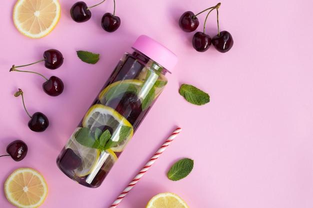 Draufsicht des aufgegossenen wassers mit kirschen und zitrone in der flasche auf der rosa oberfläche Premium Fotos