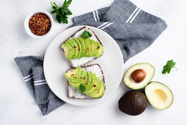 Draufsicht des avocadotoasts auf platte mit kräutern und gewürzen Kostenlose Fotos