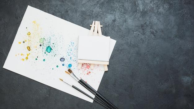 Draufsicht des befleckten gezogenen papiers mit pinsel und leerem mini gestell Kostenlose Fotos