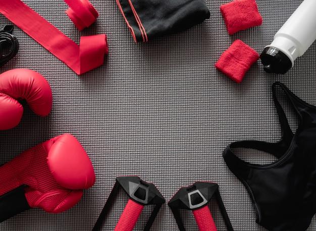 Draufsicht des box-turnhalle-konzepts mit boxhandschuh, fitness-studio-outfit, springseil und zubehör auf yogamattenhintergrund. Premium Fotos