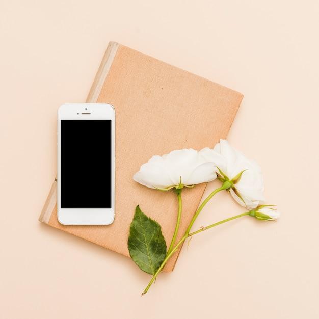 Draufsicht des buches, des smartphone und der blumen Kostenlose Fotos