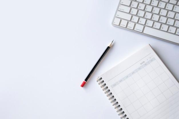 Draufsicht des büroarbeitsplatzarbeitsplatzes mit offenem buch, bleistift und tastatur auf weißem tischhintergrund. flach liegen Premium Fotos