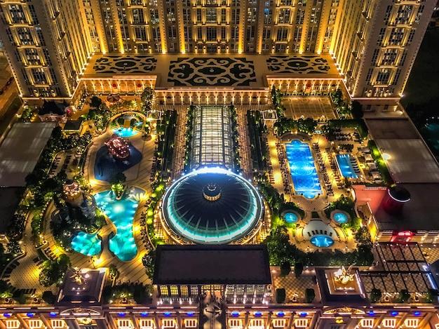 Draufsicht des dachgartens des hotels parisian in macao. nachtbeleuchtung des schwimmbades. Premium Fotos