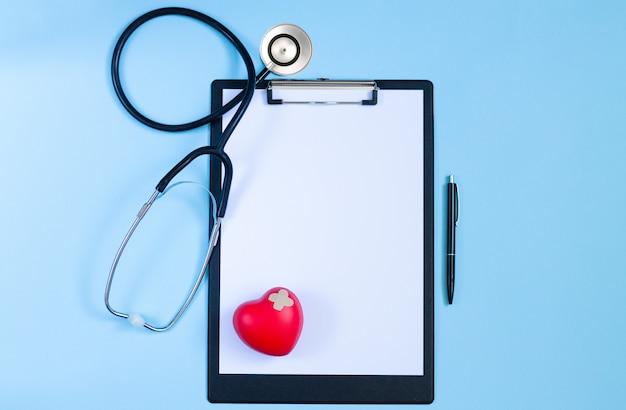 Draufsicht des doktorschreibtischs mit stethoskop, rotem herzen, stift und leerem papier auf zwischenablage. konzept der kardiologischen erkrankungen Premium Fotos
