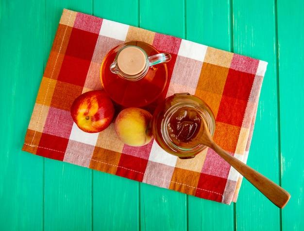 Draufsicht des frischen fruchtapfels mit pfirsich und einer flasche olivenöl und pfirsichmarmelade in einem glas mit einem holzlöffel auf karierter serviette auf grünem holzhintergrund Kostenlose Fotos
