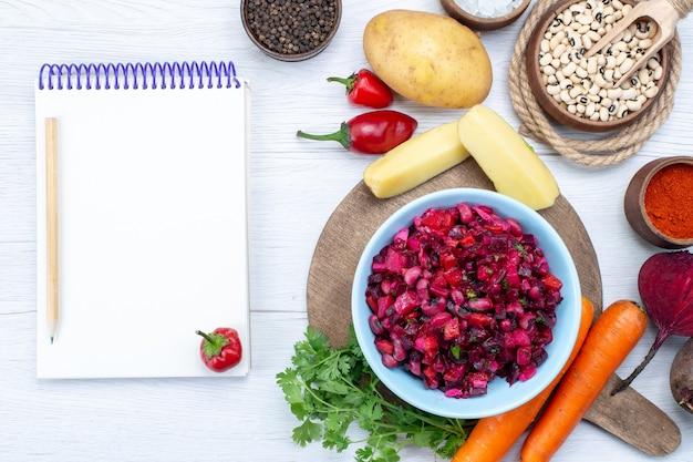 Draufsicht des frischen rübensalats mit geschnittenem gemüse zusammen mit rohen bohnen karottenkartoffeln notizblock auf hellem schreibtisch, lebensmittel mahlzeit gemüse frischer salat Kostenlose Fotos