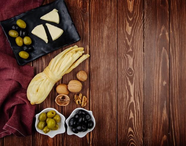 Draufsicht des frischkäses in dreiecksform mit eingelegten oliven auf einem schwarzen tablett und walnüssen mit schnurkäse auf dunklem holztisch mit kopienraum Kostenlose Fotos