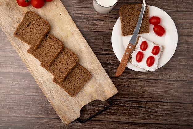 Draufsicht des frühstückssatzes mit geschnittenem roggenbrot verschmiert mit hüttenkäse und tomaten mit messer in platte auf hölzernem hintergrund Kostenlose Fotos