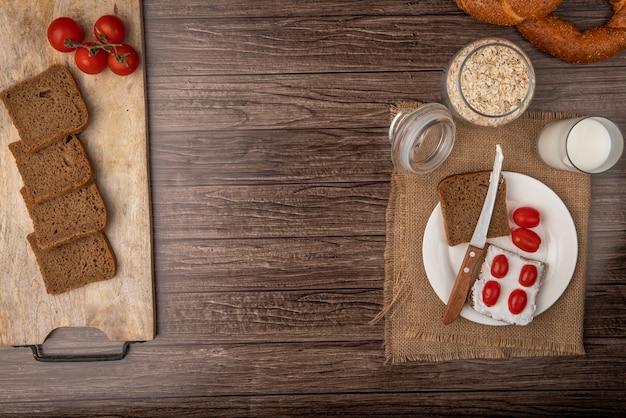 Draufsicht des frühstückssatzes mit roggenbrotscheiben, die mit hüttenkäse und tomaten mit milch und haferflocken auf hölzernem hintergrund mit kopienraum verschmiert wurden Kostenlose Fotos