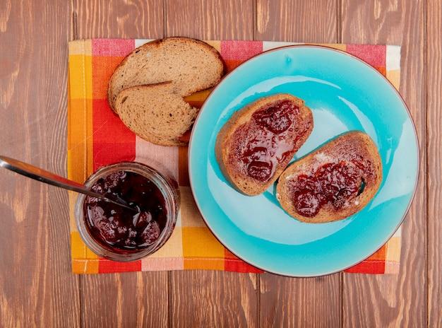 Draufsicht des frühstückssatzes mit roggenbrotscheiben, die mit marmelade in teller- und erdbeermarmeladen-roggenbrotstücken auf kariertem stoff und holztisch verschmiert wurden Kostenlose Fotos