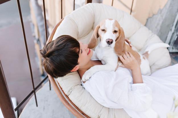Draufsicht des gebräunten brünetten mädchens, das mit lächeln auf schläfrigen beagle-hund schaut, der neben sitzt Kostenlose Fotos