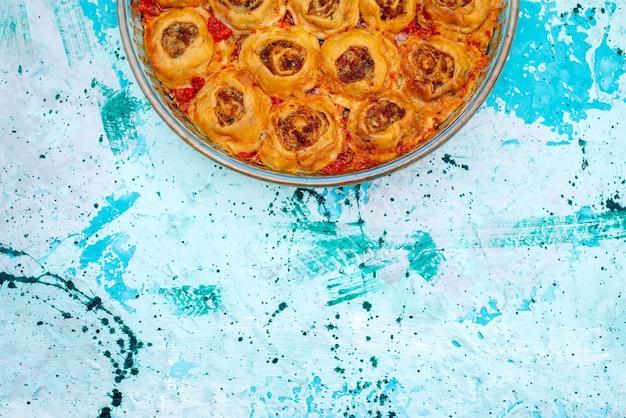 Draufsicht des gekochten teigmehls mit hackfleisch und tomatensauce innerhalb der glaspfanne auf hellblauem schreibtisch, backen sie nahrungsfleischteig Kostenlose Fotos