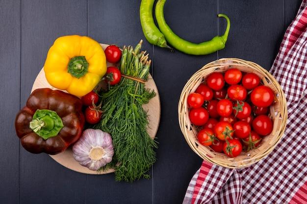 Draufsicht des gemüses als korb der tomate auf kariertem stoff mit pfeffer-tomaten-knoblauch-dillbündel auf schneidebrett auf schwarzer oberfläche Kostenlose Fotos