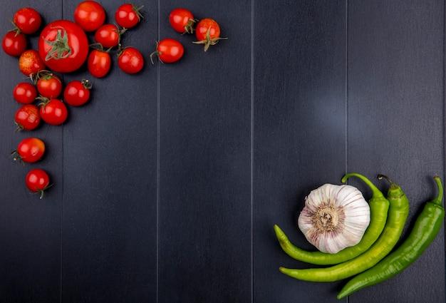Draufsicht des gemüses als tomaten-knoblauch-pfeffer auf schwarzer oberfläche Kostenlose Fotos