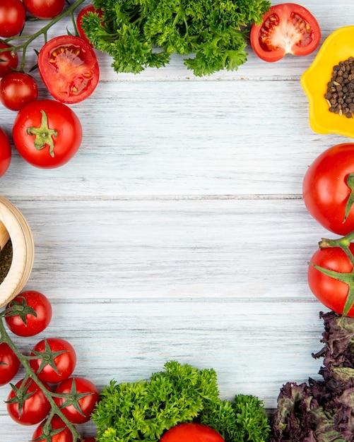 Draufsicht des gemüses als tomatenkorianderbasilikum mit knoblauchbrecher des schwarzen pfeffers auf holzoberfläche mit kopienraum Kostenlose Fotos